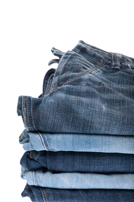 stack of blue jeans isolated on white background
