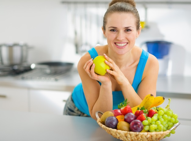 Smiling young woman holding apple in modern kitchen