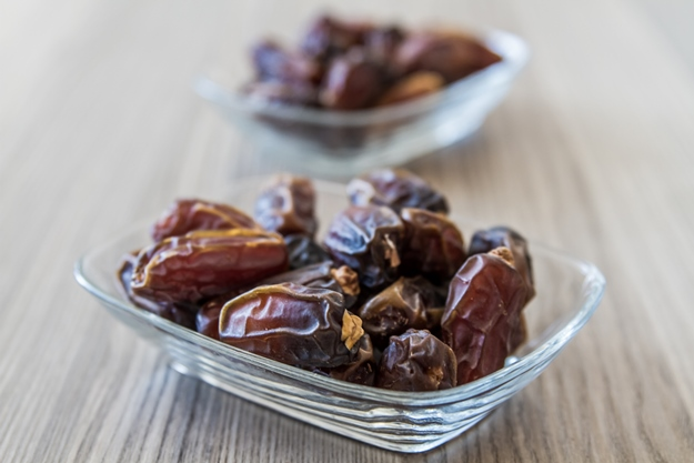Dates, traditional Ramadan fruit in glass dishes on wooden table