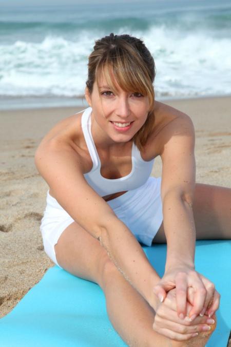 Beautiful woman stretching on a sandy beach