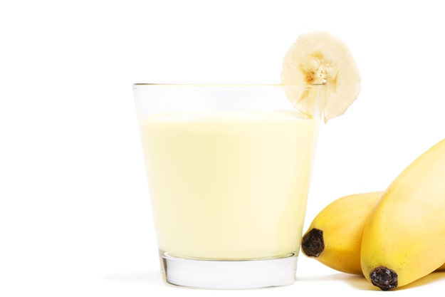 banana milkshake with a piece of banana and bananas aside on white background
