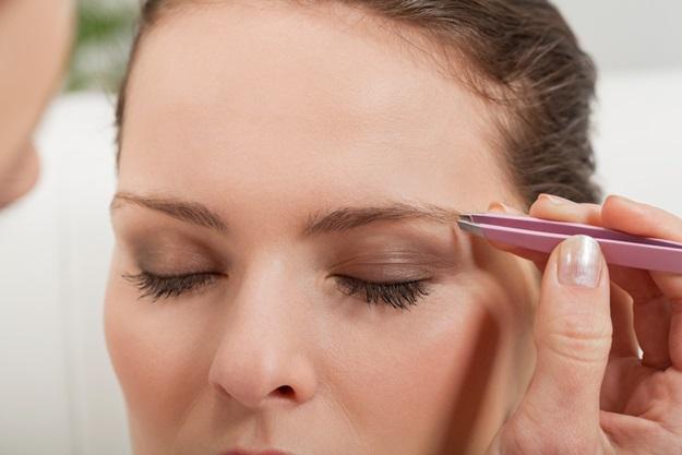 young beautiful woman eyebrow plucking tweezers eyes hair closeup portrait