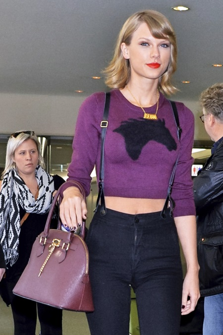 Taylor Swift leaves Narita International Airport, wearing trousers with braces, a purple cropped jumper and red ankle boots. Featuring: Taylor Swift Where: Narita, Chiba, Japan When: 08 Nov 2014 Credit: Kento Nara/Future Image/WENN.com **Not available for publication in Germany, Poland, Russia, Hungary, Slovenia, Czech Republic, Serbia, Croatia, Slovakia**