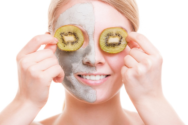 Skin care. Young woman with clay mask on her face covering eyes with slices of kiwi fruit. Girl taking care of her dry compexion. Isolated. Spa and beauty treatment.